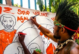 "An event attendee colors a banner at an ""Orange the World"" event"
